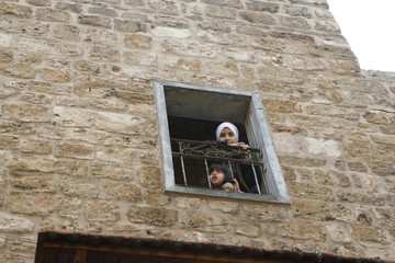 "Lebanese children look from their home's window at the traditional soap factory called ""Khan al Saboun"" in Tripoli's old souk district"