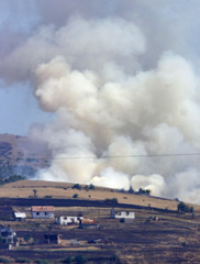 SMOKE RISES FROM A HOUSE HIT BY MACEDONIAN SHELL IN ARACINOVO.