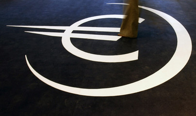 A woman walks on the symbol for the euro during the inauguration of an exhibition on the 10th anniversary of the currency in Lisbon