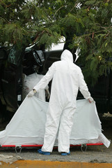 Forensic worker holds a white sheet to block the view of the body of a man killed in a drive-by-shooting attack in Monterrey