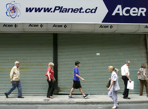 PEDESTRIAN WALK PAST CLOSED DOORS OF A COMPUTER STORE IN BUENOS AIRES.