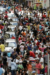 Commuters and traders crowd at a market in a busy commercial street in Sao Paulo