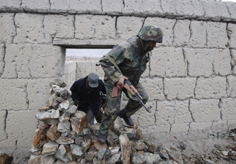 An Afghan army soldier leaves a farmer's house in Semkar village