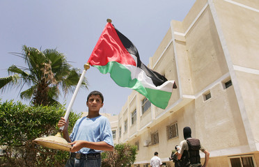 Boy holds a Palestinian flag after Hamas fighters captured Preventive Security headquarters (background) in Gaza
