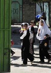 Afghan school girls wave to German armed forces Bundeswehr soldiers during a visit to a school in Taloqan, east of Kundus