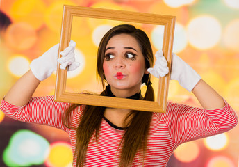 Closeup portrait of cute curious young girl clown mime holding wooden frame looking to the side
