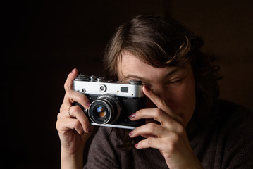 A woman is photographing a retro camera on a dark background.
