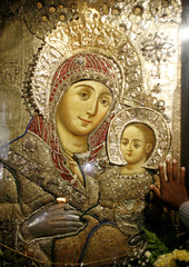 A worshipper places his hand on an icon at the Nativity church in Bethlehem