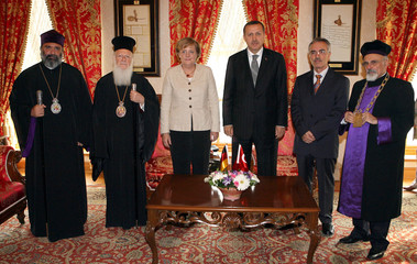 Visiting German Chancellor Angela Merkel and Turkish Prime Minister Tayyip Erdogan pose with the four religious leaders at the prime minister's office in Istanbul