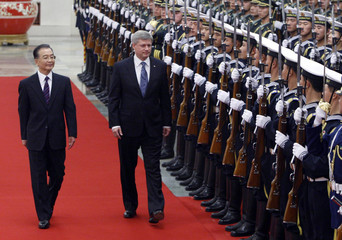 China's Premier Wen Jiabao and Canada's Prime Minister Stephen Harper inspect honour guards during a welcome ceremony at the Great Hall of the People in Beijing