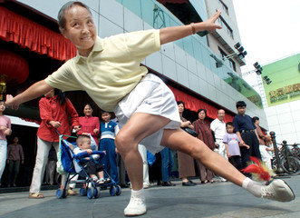 CHINESE ELDERLY WOMAN PERFORMS WITH A SHUTTLECOCK IN BEIJING.