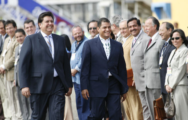 Peru's President Garcia and Ecuador's President Correa walk in front of Ecuador's ministerial cabinet after their arrival in Tumbes