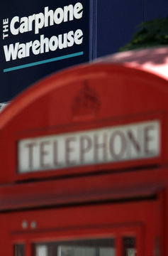 Signage for a Carphone Warehouse store is pictured above a traditional telephone booth in central London