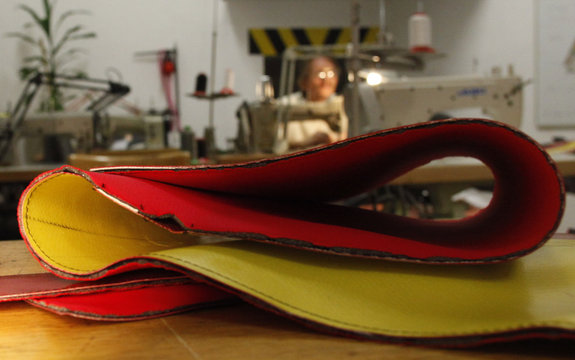A worker sews a bag made of old plastic lorry covers in the workshop of the Gabarage design shop in Vienna