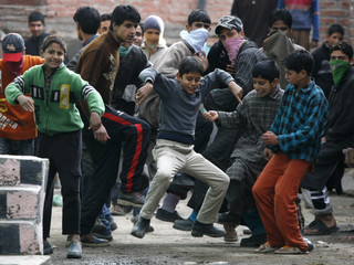 Kashmiri protesters taunt Indian policemen during an anti-poll protest in Srinagar