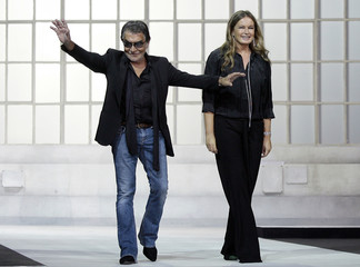 Designer Cavalli and his wife Eva acknowledge the applause at the end of the Just Cavalli Spring/Summer 2010 women's collection in Milan