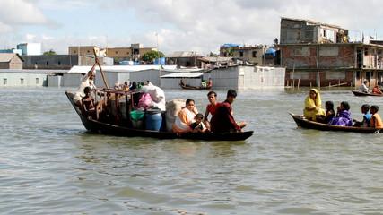Family leaves their flooded home in Kamrangir Char in the Bangladesh capital Dhaka.