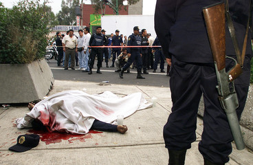 FILE PHOTO OF DEAD POLICEMAN IN CRIME PLAGUE MEXICO CITY KILLER IN ASHOOTOUT WITH ROBBERS.
