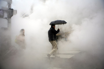 Pedestrians walk through steam coming from grates along a street in New York