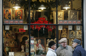 Polish people talk in front of a shop selling souvenirs with religious symbols in the old town in Warsaw