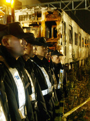 SOUTH KOREAN RIOT POLICEMEN STAND GUARD AS THE TRAIN DAMAGED BY FIRE ISBROUGHT TO WOL-BAE ...