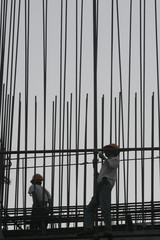 Men work at a construction site in Hanoi