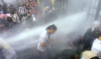 AN INDONESIAN STUDENT PROTESTER IS HIT WITH A JET OF WATER IN JAKARTA.
