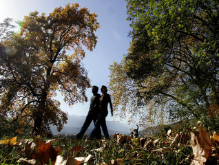 A couple is silhouetted as they walk through a park covered with autumn leaves in Innsbruck
