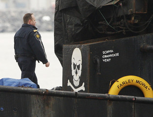 A Canadian federal official walks past a skull and crossbones sign painted on the Sea Shepherd Conservation Society vessel Farley Mowat, shortly after it was brought into Sydney