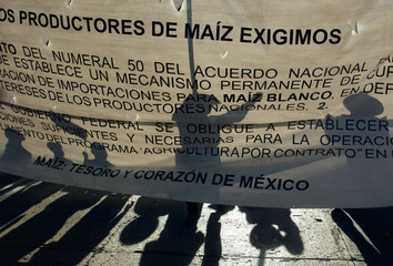 The silhouette of protesters are seen on a banner during a march on the streets of Mexico City