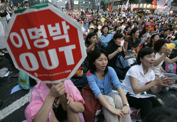 People shout slogans during a rally to demand the full-scale renegotiation of the U.S. beef import deal and the resignation of South Korean President Lee in front of Seoul City Hall