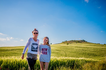 Fillette et femme devant le Paysage du Val d'Orcia en Toscane au soleil couchant