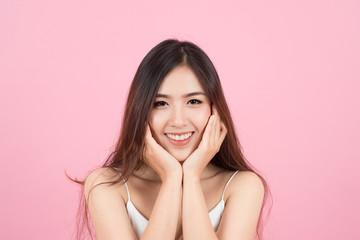 Asian young beautiful woman smiling and touch her face like a v-shape isolated over pink background. Cleaning face, perfect skin. SPA therapy, skincare, cosmetology and plastic surgery concept