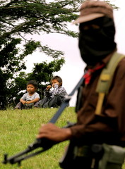 High-Resolution File - A member of Zapatista National Liberation Army (EZLN) stand guard near a meeting.