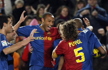 Barcelona's Henry, Puyol and teammates celebrate a goal against Sporting Gijon during their Spanish first division soccer league match in Barcelona