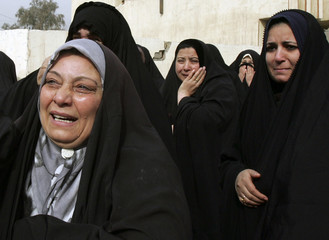 Iraqi women weep during the funeral of a relative who was gunned down in Baghdad