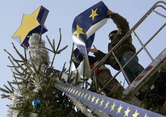 Workers arrange decorations inspired by the European Union symbol on a Christmas tree in central Bucharest
