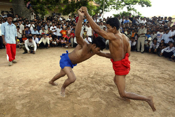 Cambodian men wrestle each other at Virhear Sour village in Kandal province