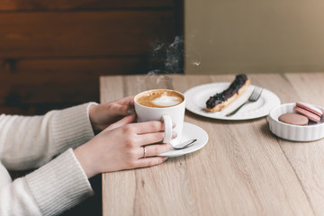 Womans hands wrapped around a cup on wood table with chocolate eclair