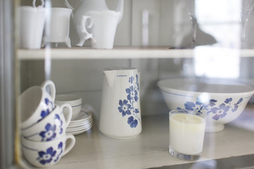 white and blue pottery in a cupboard