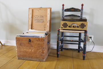 box with gramophone records next to a record player