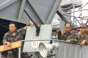 PHILIPPINE SOLDIERS STAND BESIDE A 50MM CALIBER MACHINE GUN ABOARD A PHILIPPINE NAVY SHIP IN ...