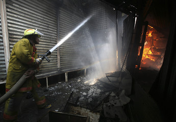 Firefighters put out the flames of a market fire that destroyed hundreds of stalls selling clothes in Managua