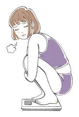体重計に乗って落ち込む女性