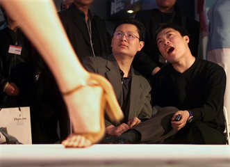 CHINESE MEN ADMIRE A MODEL'S CLOTHES ON THE CATWALK AT THE 10TH CHINA INTERNATIONAL CLOTHING AND ...