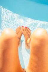 Crop shot of female feet in pool