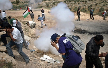 Palestinian demonstrators and International peace activists run away from a stun grenade explosion in Bilin