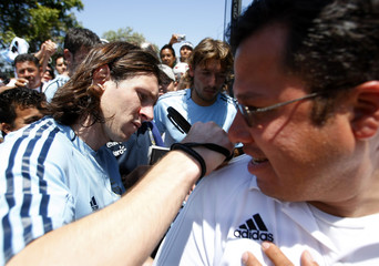 Argentina's Messi signs shirt of fan before boarding team bus following training session in San Diego