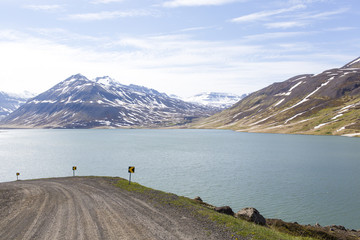 Gravel road near a lake in the mountains of Iceland.