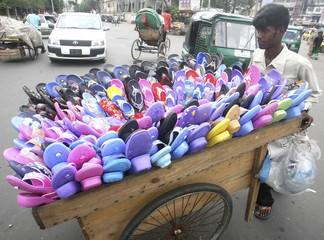A street trader pushes his cart of footwear in Dhaka